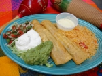 Taquitos Tapatios - Two crispy roll taquitos filled with cheese, poblano pepper and your choice of grilled chicken or shrimp. Served with cheese dip for dipping and your choice of rice or beans.